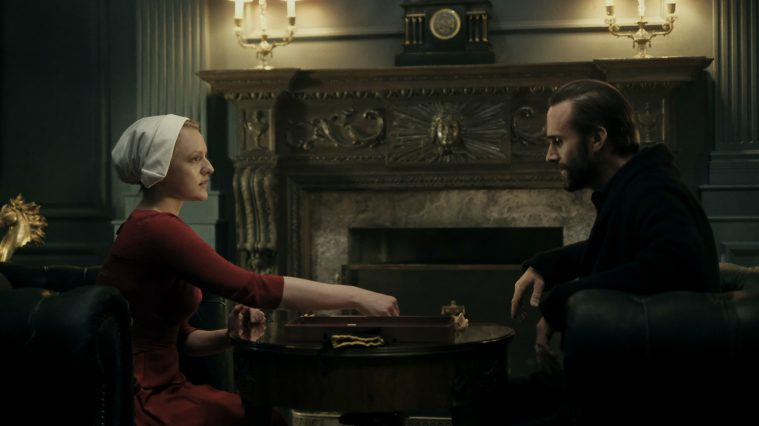 "The Handmaid's Tale -- ""Birth Day"" -- Episode 102 -- Offred and her fellow Handmaids assist with the delivery of Janine's baby, prompting Offred to recall her own daughter's birth. Offred draws closer to Ofglen while dreading a secret meeting with the Commander. Offred (Elisabeth Moss) and Commander Waterford (Joseph Fiennes), shown. (Photo by: George Kraychyk/Hulu)"